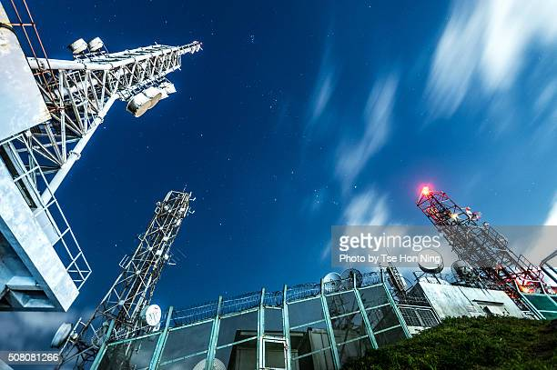 Starry night sky with radio tower from below