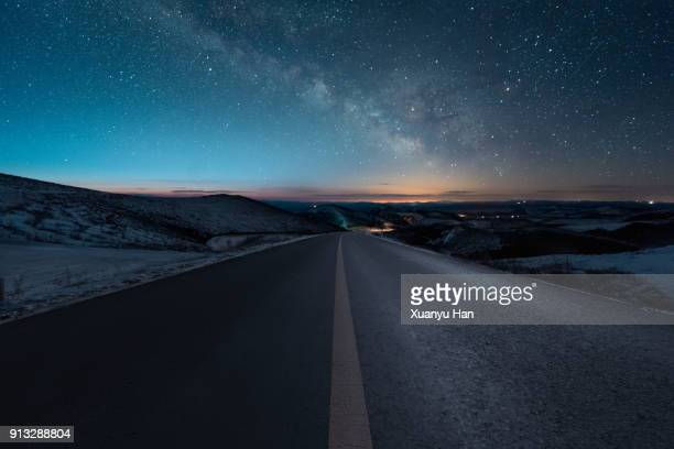 starry night with empty windy road - night stockfoto's en -beelden