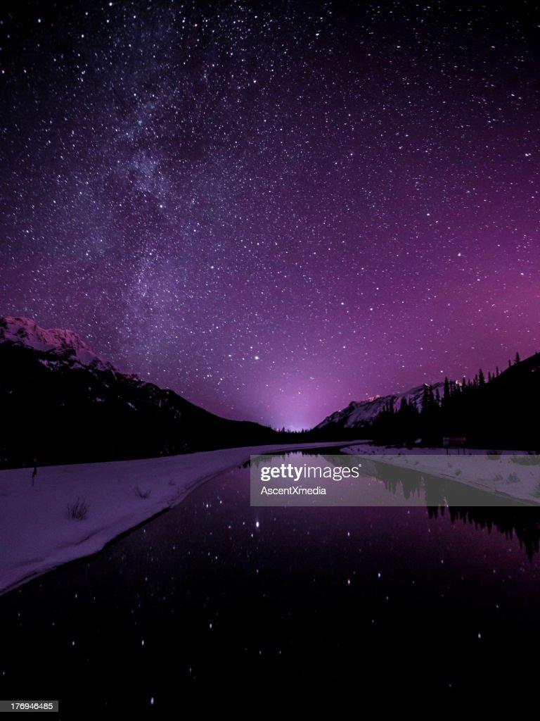 Starry sky illuminates mountain landscape : Stock Photo