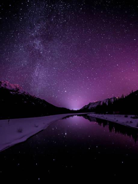 Starry sky illuminates mountain landscape