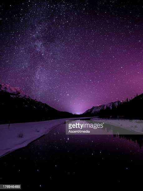 Starry sky illuminates mountain landscape