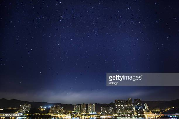 Starry sky over city skyline with light pollution