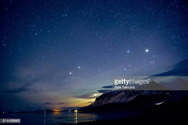 Starry sky over still ocean in arctic landscape