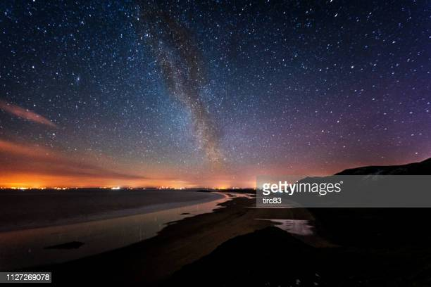 starry sky over welsh beach - gower peninsula stock photos and pictures
