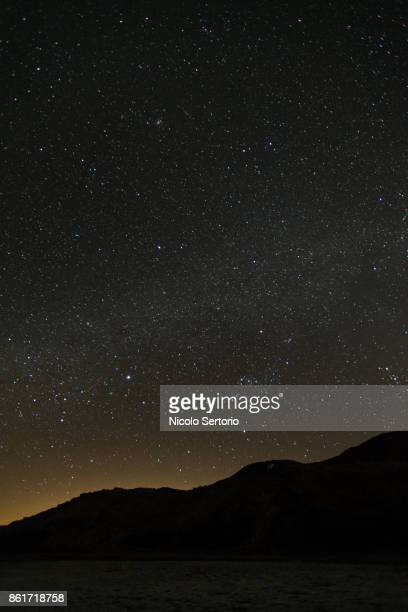 Stars and city lights behind mountain range from the Mojave desert