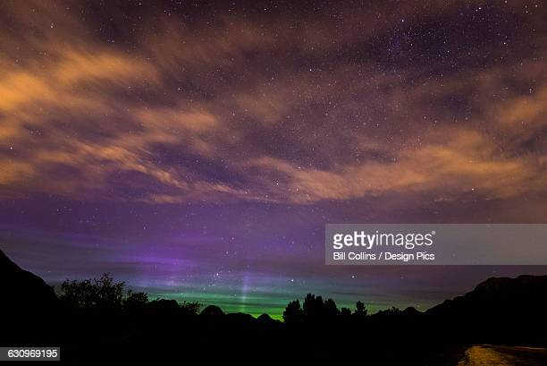 Stars and the Northern Lights (Aurora Borealis) shine through high clouds over Pitt Lake