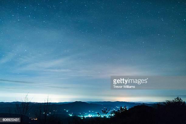 stars fill the sky above small village - night - fotografias e filmes do acervo
