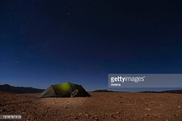 Stars in cloudless sky at night and dome tent with touring bicycle of adventurous hiker on high plateau of the Altiplano, Potosí Department, Bolivia.