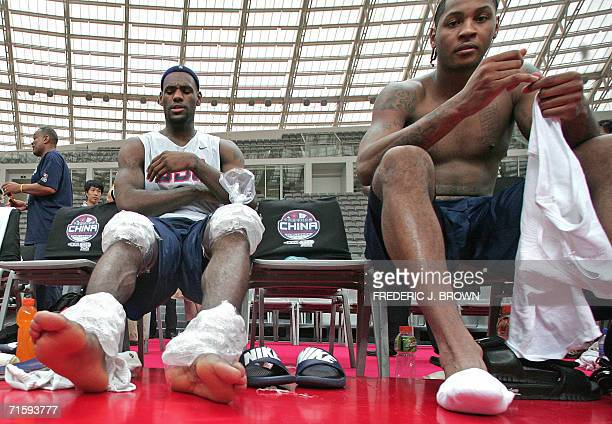 NBA stars LeBron James of the Cleveland Cavaliers receives icetreatment on his knees and ankles while seated beside Carmelo Anthony of the Denver...