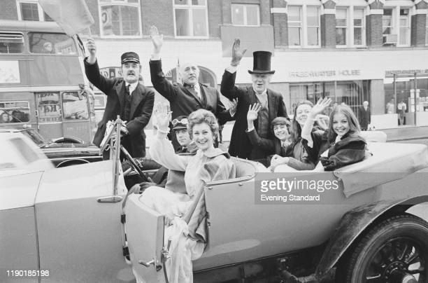 Stars of the British drama film 'The Railway Children' wave to spectators from a vintage car in London on the day of the film's premiere, 21st...