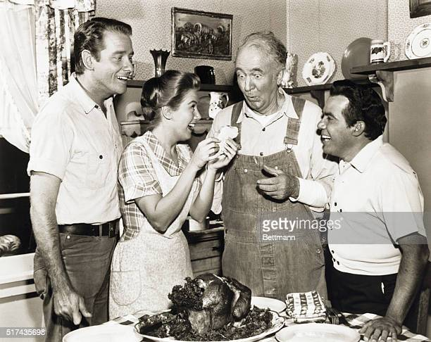 Stars of The Real McCoys Dick Crenna Kathy Nolan and Walter Brennan having some fun around the dinner table The man at the immediate right is...