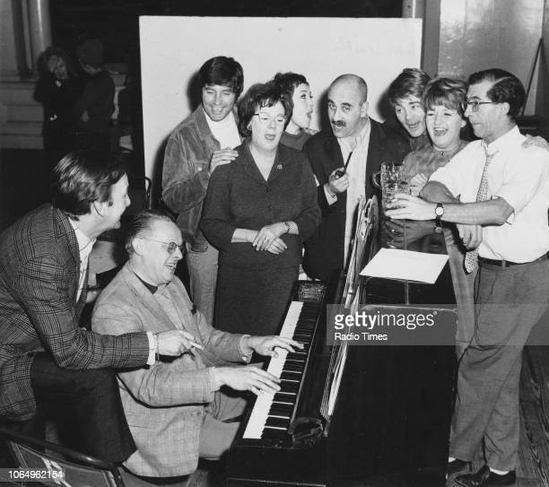 Stars of the television sitcom 'Till Death Us Do Part' pictured singing around a piano Johnny Speight Dennis Wilson Jimmy Tarbuck Dandy Nichols Una...
