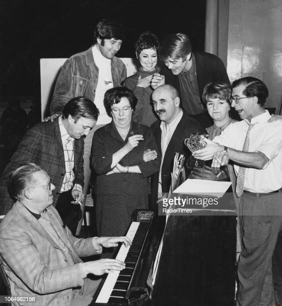 Stars of the television sitcom 'Till Death Us Do Part' pictured singing around a piano Dennis Wilson Johnny Speight Jimmy Tarbuck Dandy Nichols Una...