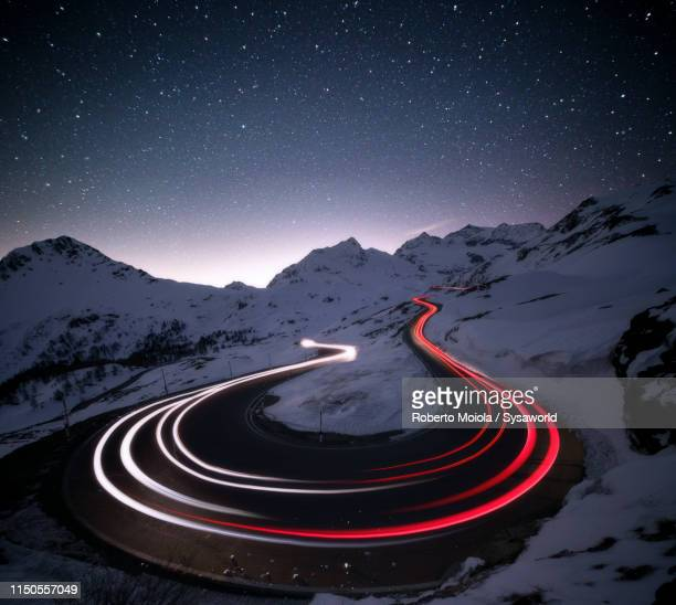 stars on car trails lights, bernina pass, engadin, switzerland - turning stock pictures, royalty-free photos & images