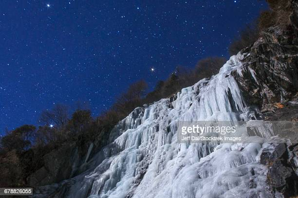 Stars shine above an icefall on a moonlit night in China.