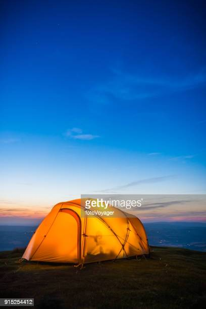 Stars shining above illuminated tent high on mountain after sunset