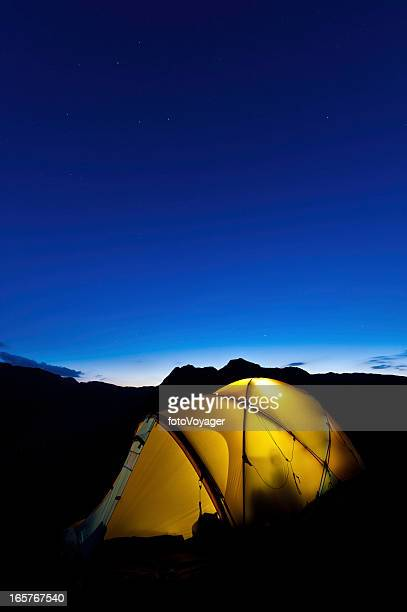 Stars shining above yellow dome tent mountain peaks