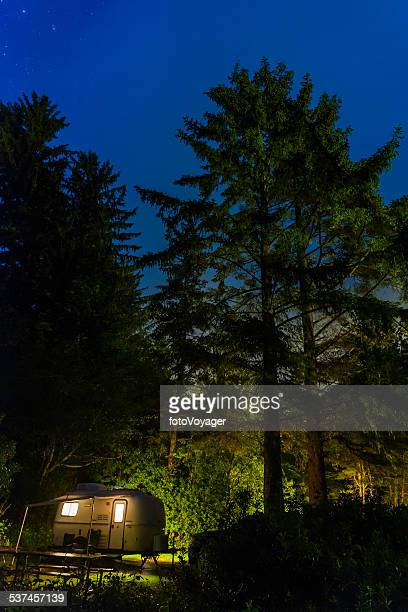 Stars shining over illuminated trailer forest campsite Pacific Northwest USA
