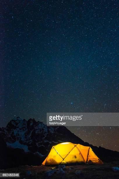 Stars shining over warmly illuminated camping tent Himalaya mountains Nepal