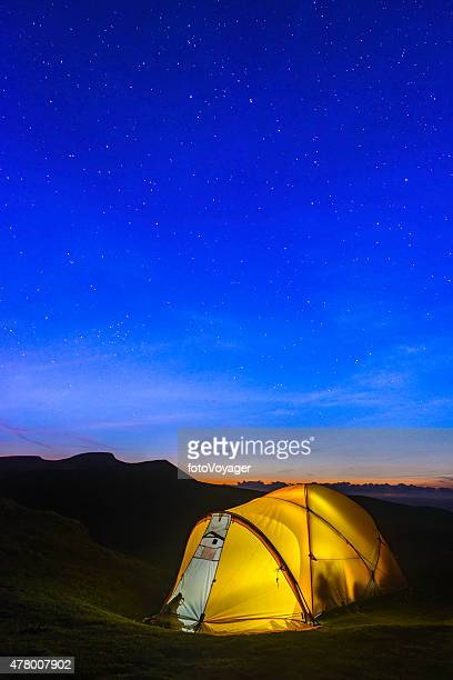 Stars shining over yellow dome tent illuminated in mountain camp