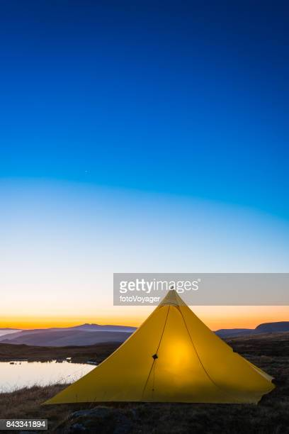 Stars shining over yellow tent camping beside mountain lake sunrise