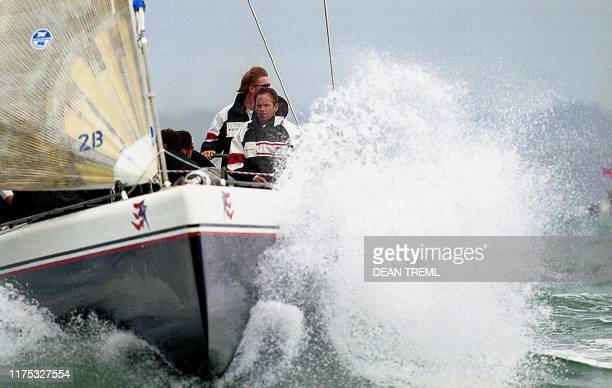 Stars & Stripes creates a splash under the watchfull eye of a crewman as it races Hawaii's Abracadabra 2000 09 November 1999 in choppy seas on the...