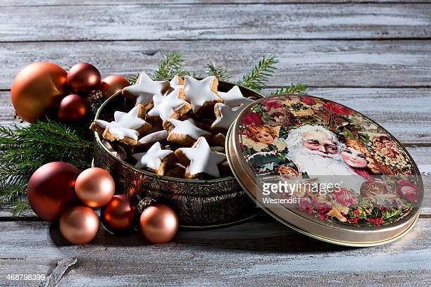 Star-shaped cinnamon cookies in a christmas tin, studio shot