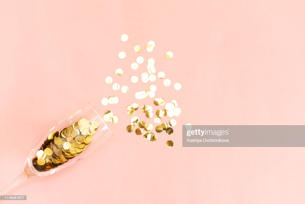 Star-shaped silver confetti poured out of champagne glass on pink background with copy space for text. Top view. Holiday and celebration concept. : Stock Photo