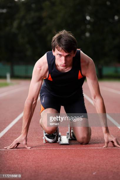 start of a 100m race - men's track stock pictures, royalty-free photos & images