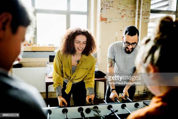 start up business colleagues playing table soccer - freizeit stock-fotos und bilder