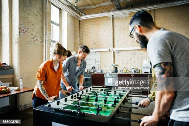 Start up business colleagues playing table soccer