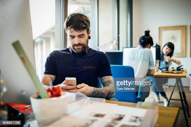 Start up business man with smart phone sitting on desk
