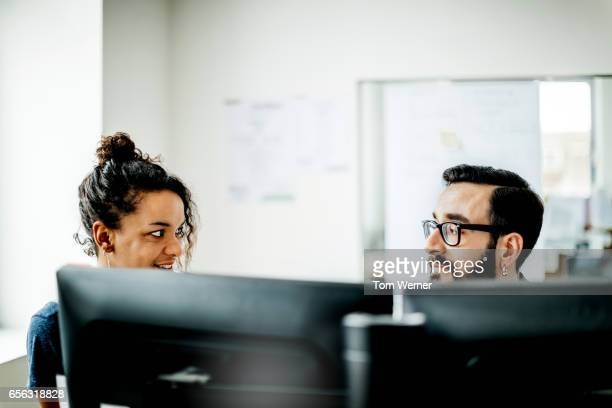 start up business people having an informal meeting at a desk - southern european descent stock pictures, royalty-free photos & images