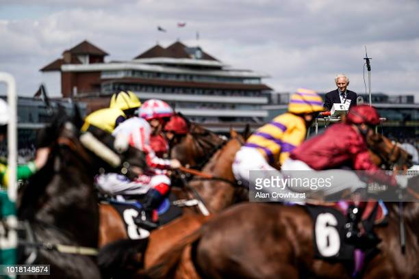 Starter Bob Mann looks on as runners leave the starting stalls at Newbury Racecourse on August 17 2018 in Newbury United Kingdom