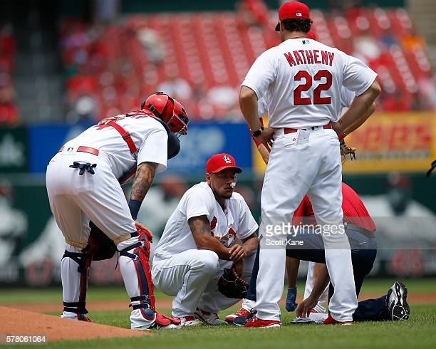 Starter Carlos Martinez of the St Louis Cardinals is tended to by a trainer as Yadier Molina and manager Mike Matheny look on during the second...