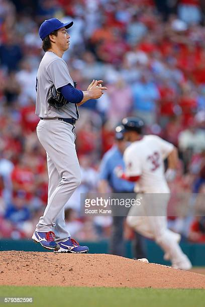 Starter Kenta Maeda of the Los Angeles Dodgers pauses on the mound as Matt Adams of the St. Louis Cardinals runs the bases after hitting a solo home...
