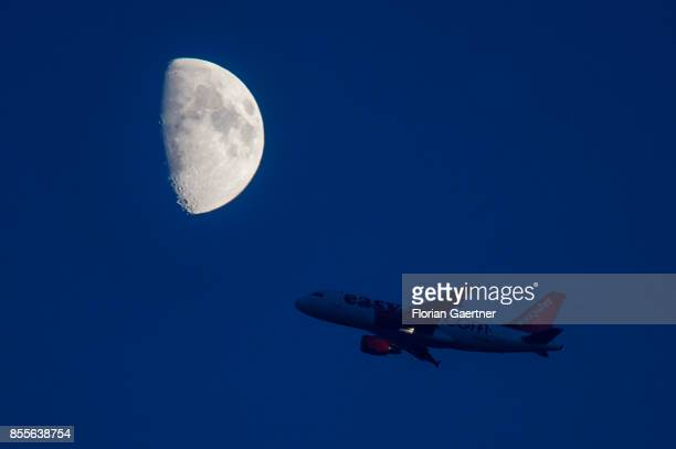A startin plane of the airline 'easyjet' is pictured in front of the rising moon on September 29 2017 in Berlin Germany