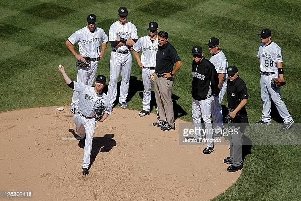 Starting pitcher Aaron Cook of the Colorado Rockies throws a few pitches in front of a trainer Manager Jim Tracy pitching coach Bob Apodaca and the...