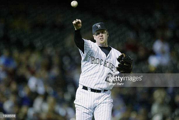 Starting pitcher Aaron Cook of the Colorado Rockies throws to first base against the San Diego Padres at Coors Field on April 18 2003 in Denver...