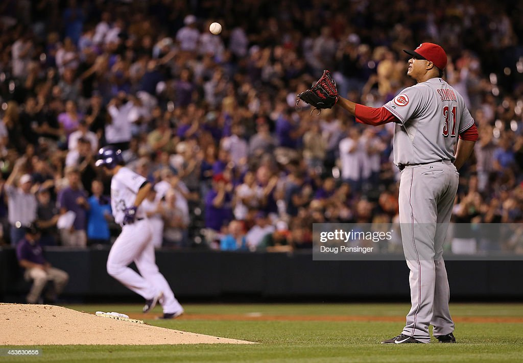 Starting pitcher Alfredo Simon #31 of the Cincinnati Reds collects the ball after giving up a three run home run to Charlie Culberson #23 of the Colorado Rockies in the fifth inning at Coors Field on August 14, 2014 in Denver, Colorado. The Rockies defeated the Reds 7-3.