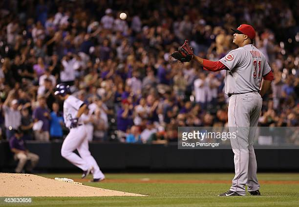 Starting pitcher Alfredo Simon of the Cincinnati Reds collects the ball after giving up a three run home run to Charlie Culberson of the Colorado...