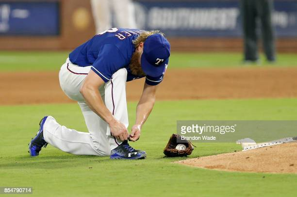 Starting pitcher Andrew Cashner of the Texas Rangers stops to tie his shoe during the fourth inning of a baseball game against the Houston Astros at...