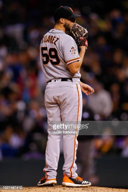 Starting pitcher Andrew Suarez of the San Francisco Giants reacts after giving up a home run to Trevor Story of the Colorado Rockies during the...