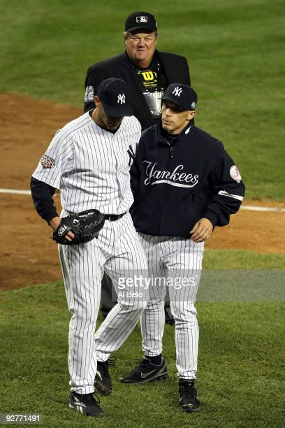 Starting pitcher Andy Pettitte of the New York Yankees is held back by manager Joe Girardi as Pettitte argues with home plate umpire Joe West at the...