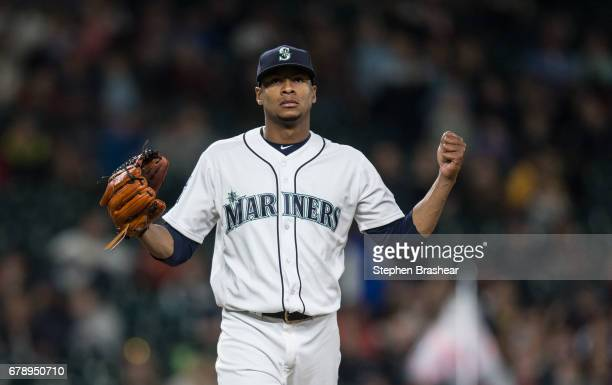 Starting pitcher Ariel Miranda of the Seattle Mariners reacts as he walks off the field after pitching the seventh inning game against the Los...