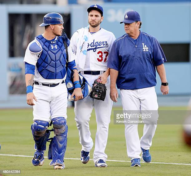 Starting pitcher Brandon Beachy walks from the bullpen to the dugout with catcher Yasmani Grandal and pitching coach Rick Honeycutt to make his...