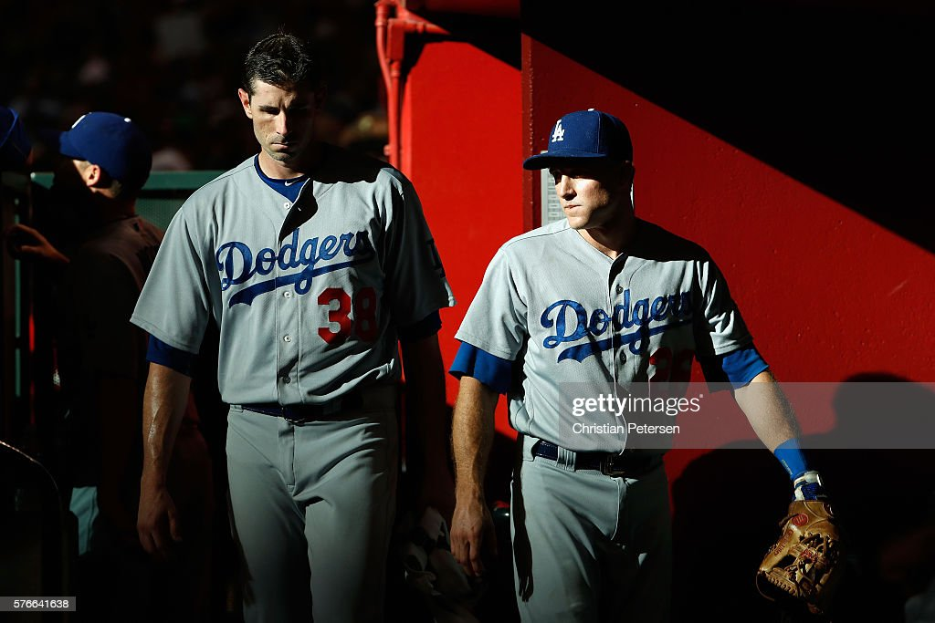 Starting pitcher Brandon McCarthy #38 and infielder Chase Utley #26 of the Los Angeles Dodgers walk though the dugout during a break from the first inning of the MLB game against the Arizona Diamondbacks at Chase Field on August 16, 2016 in Phoenix, Arizona.