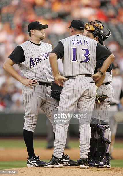 Starting pitcher Brandon Webb of the Arizona Diamondbacks reacts as coach Mark Davis comes out to the mound with catcher Juan Brito during a rough...