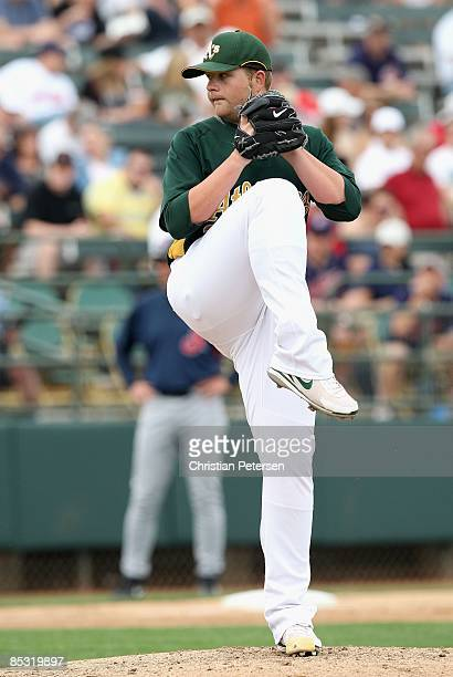 Starting pitcher Brett Anderson of the Oakland Athletics pitches against the Cleveland Indians during the spring training game at Phoenix Municipal...