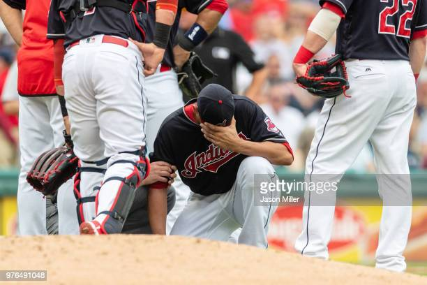 Starting pitcher Carlos Carrasco of the Cleveland Indians gets attention from a trainer after being hit by a line drive off the bat of Joe Mauer of...
